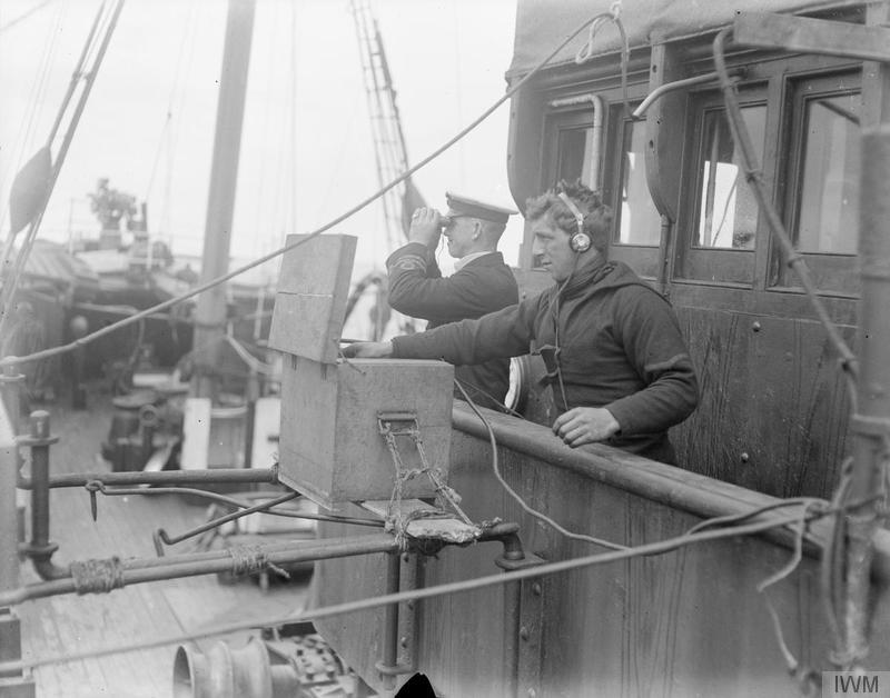 A sailor listening on a hydrophone and an officer using binoculars on board a British armed trawler © Imperial War Museum.
